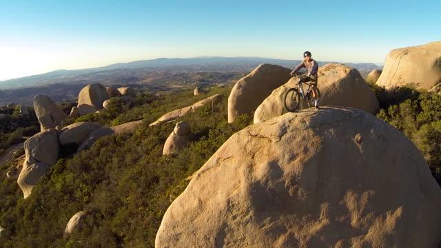 vídeos de stock, filmes e b-roll de aerial shot of young man mountain biker resting with his bike on a boulder. - goodsportvideo