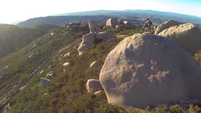 vídeos y material grabado en eventos de stock de aerial shot of young man mountain biker resting with his bike on a boulder. - sólo hombres jóvenes