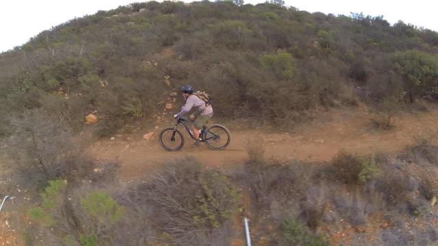 vídeos y material grabado en eventos de stock de aerial shot of young man mountain biking down a hillside trail. - slow motion - sólo hombres jóvenes