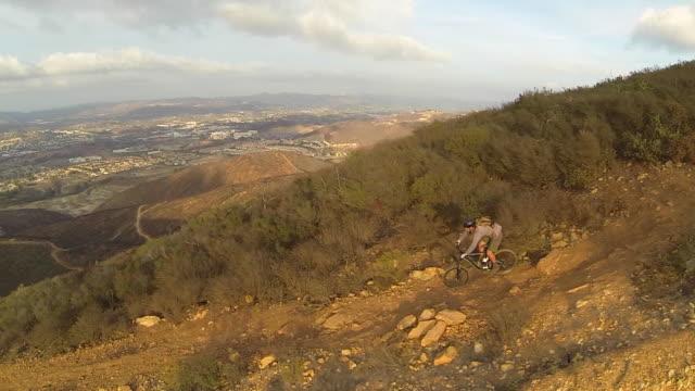 vídeos de stock, filmes e b-roll de aerial shot of young man mountain biking down a hillside trail. - goodsportvideo