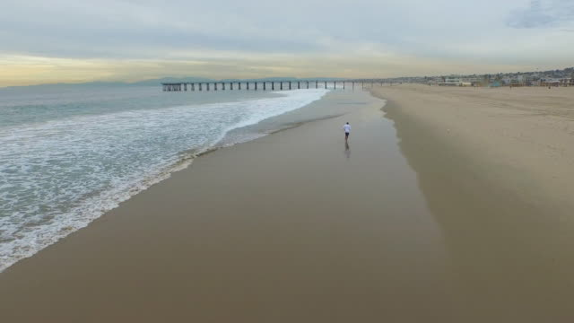 aerial shot of young man running on the beach. - one man only stock videos & royalty-free footage