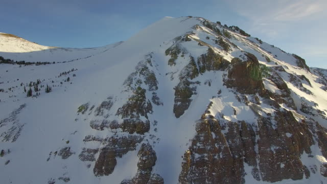 aerial shot of young men snowboarding from the top of a mountain. - pulverschnee stock-videos und b-roll-filmmaterial