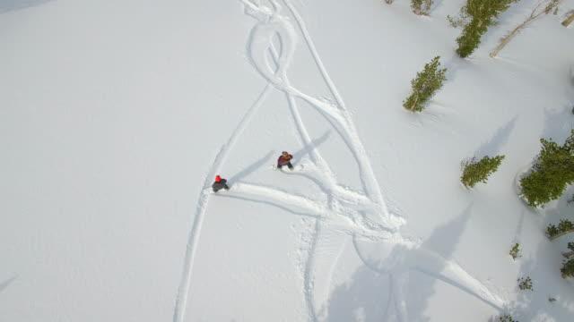 vídeos de stock e filmes b-roll de aerial shot of young men snowboarding in the mountains. - snowboard