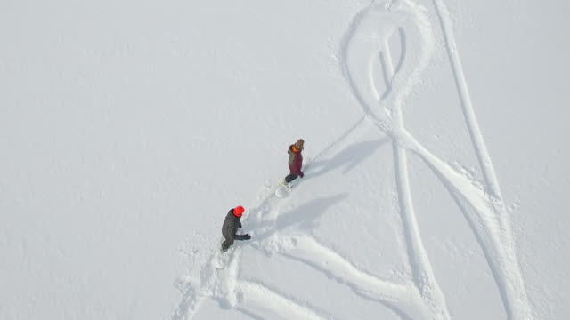 vídeos y material grabado en eventos de stock de aerial shot of young men snowboarding in the mountains. - snowboard