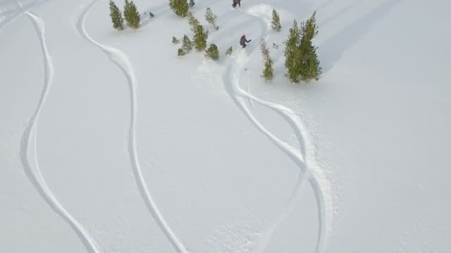 aerial shot of young men snowboarding in the mountains. - snowboard stock-videos und b-roll-filmmaterial