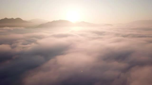 stockvideo's en b-roll-footage met luchtfoto schot op de wolken boven de wolken met zonsopkomst tijd, dromen en inspiratie concept - loopbaar bewegend beeld