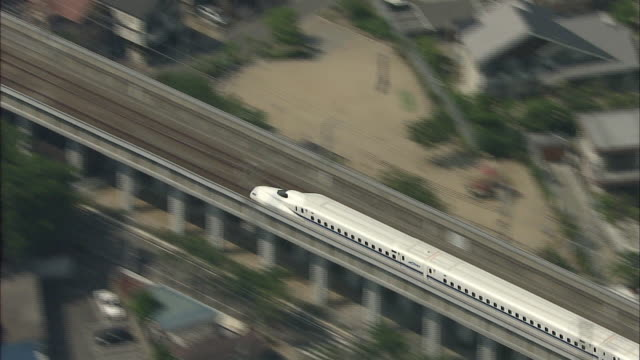 aerial shot one of the latest n700series shinkansen trains leaving shinōsaka station zooming in on the front car of the train zoom out - shinkansen stock videos & royalty-free footage