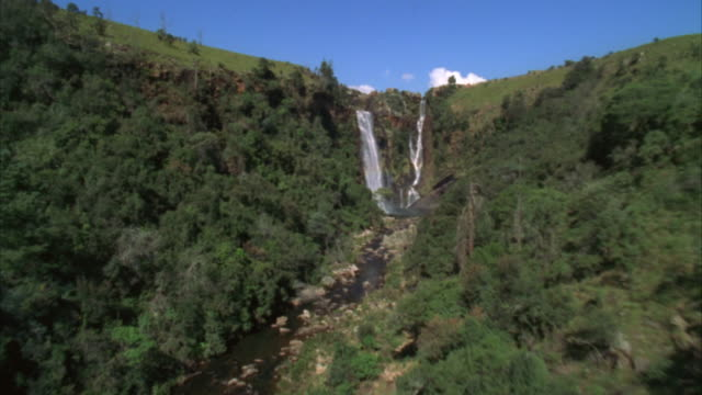 aerial shot over a lush green river canyon towards some waterfall then over a rocky river - sabie stock videos and b-roll footage