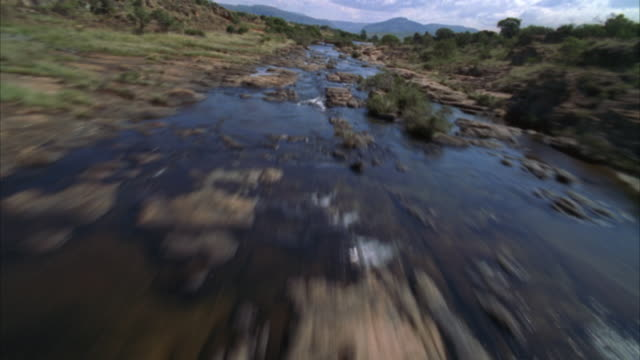aerial shot over a rocky river then over the edge of a cliff to a river canyon - mpumalanga province stock videos and b-roll footage