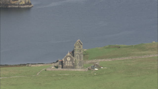stockvideo's en b-roll-footage met aerial shot over a small church on the isle of canna in the scottish inner hebrides.  - eiland