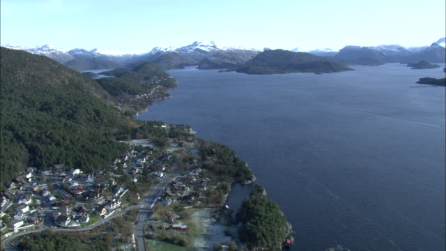 Aerial shot over a small town and forested mountains on the coast of western Norway.