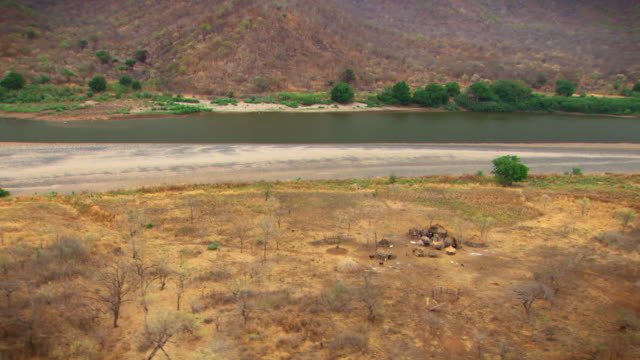 aerial shot over a tiny village on the banks of the blue nile near the grand ethiopian renaissance dam in ethiopia.  - ethiopia stock videos and b-roll footage