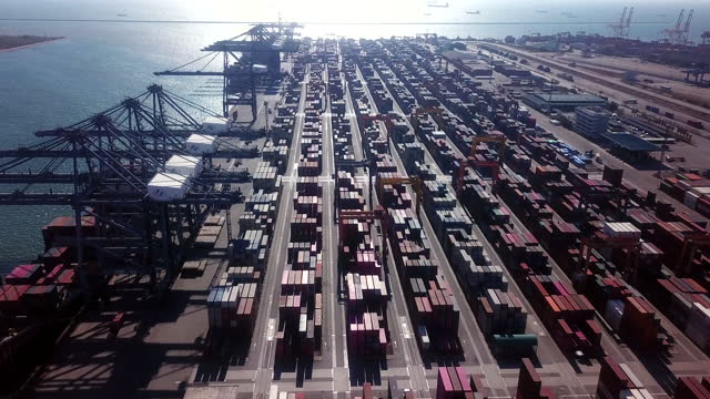 aerial shot over container yard and cargo ship in pier - global finance stock videos & royalty-free footage