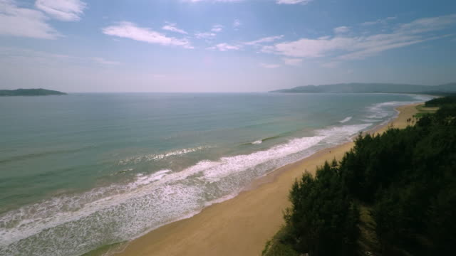 aerial shot over empty beach at yalong bay in sanya, hainan province, china. tropical paradise - spoonfilm stock-videos und b-roll-filmmaterial