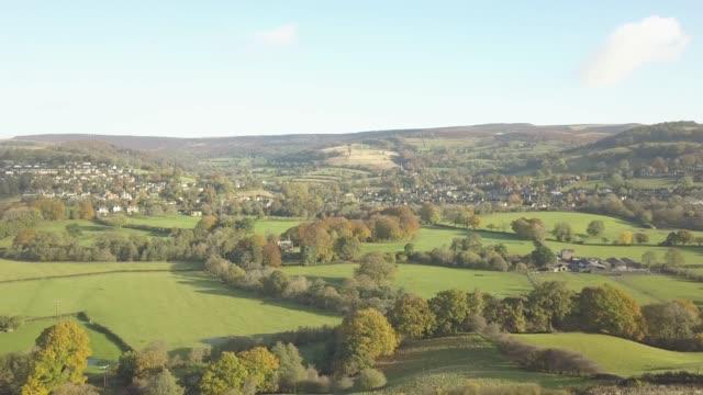 aerial shot over fields towards hathersage in autumn, hathersage, peak district national park, derbyshire, england, united kingdom, europe - hill stock videos & royalty-free footage