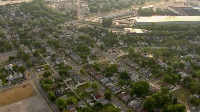 Aerial shot over houses and warehouses in Detroit neighborhoods.
