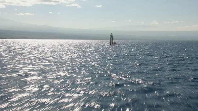 big island, hawaii - november 8, 2010: aerial shot over ocean, flying over a lone catamaran. - sailing stock videos & royalty-free footage