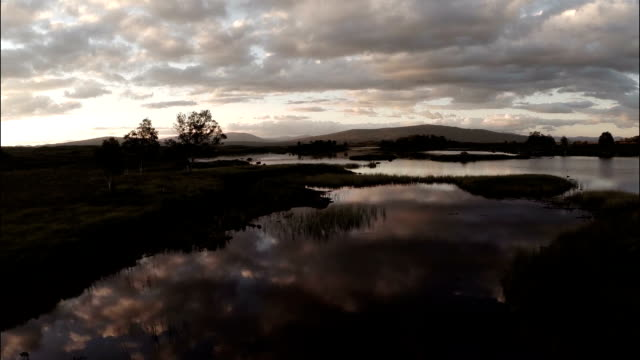 Aerial shot over Rannoch moor in Scotland revealing a desolate and baron landscape during sunset