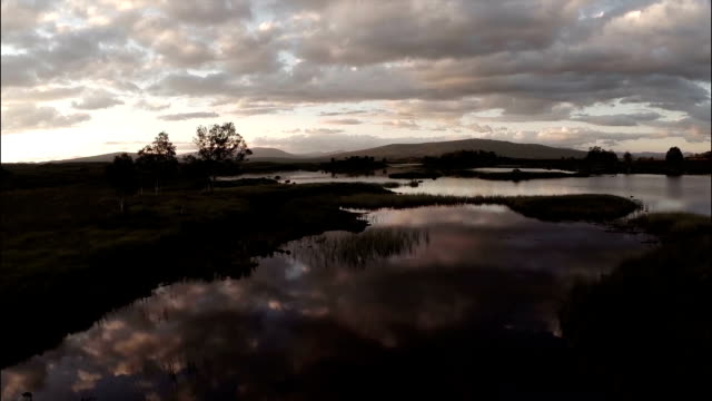 Aerial shot over Rannoch moor in Scotland revealing a desolute and baron landscape during sunset