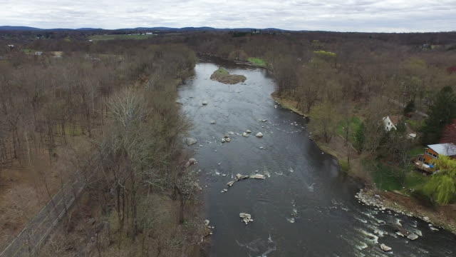 vidéos et rushes de aerial shot over river flanked by quiet road, small houses, and bare winter trees - arbre sans feuillage