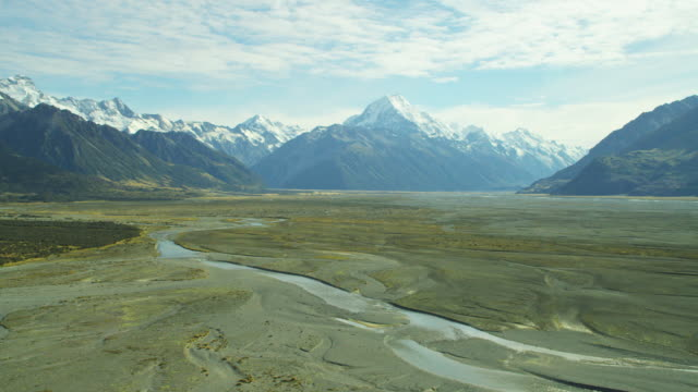 aerial shot over riverbed with snowcapped mountains - new zealand southern alps stock videos & royalty-free footage