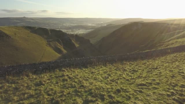 aerial shot over winnats pass at sunrise, castleton, hope valley, peak district national park, derbyshire, england, united kingdom, europe - tracking shot stock videos & royalty-free footage