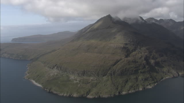 Aerial shot past the mountinous coastline of Skye.