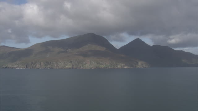 aerial shot past the mountinous coastline of skye.  - hebrides stock videos & royalty-free footage