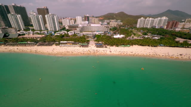 aerial shot pulling away from crowded beach in sanya, hainan province, china. - spoonfilm stock-videos und b-roll-filmmaterial