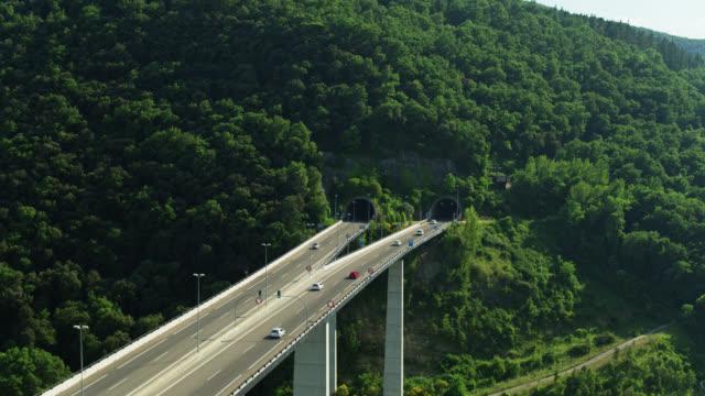 カステルフォリット・デ・ラ・ロカ付近の高速道路橋とトンネルから引き戻す空中ショット - カタルーニャ州点の映像素材/bロール