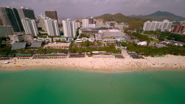 aerial shot pulling up and away from crowded beach in sanya, hainan province, china. - spoonfilm stock-videos und b-roll-filmmaterial