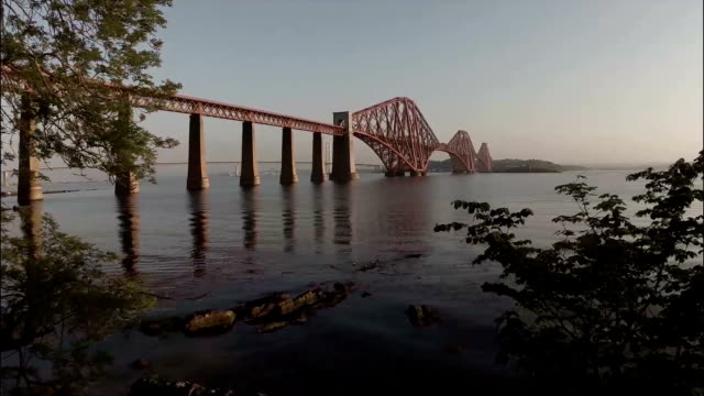 Aerial shot revealing the Forth Rail Bridge outside Edinburgh during sunrise on a calm summer morning