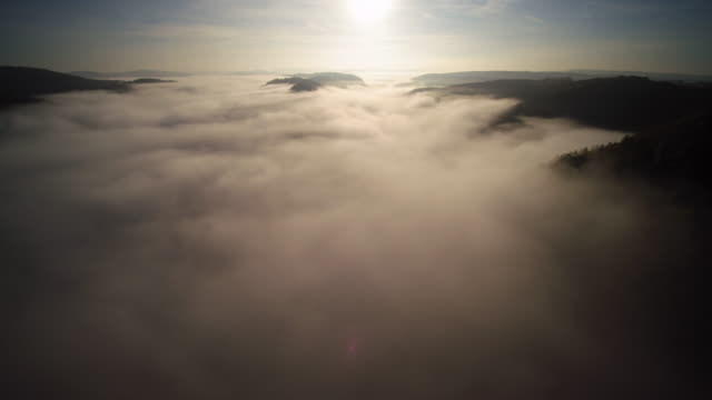 aerial shot rising sun and thick fog over river valley with mountains - spiritualität stock-videos und b-roll-filmmaterial
