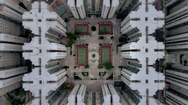 vídeos de stock e filmes b-roll de aerial shot rising up showing tennis courts at the centre of an apartment complex in whampoa garden, hong kong - design