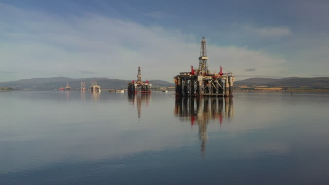 aerial shot showing offshore oil platforms resting in cromarty firth, scotland, united kingdom - industrial equipment stock videos & royalty-free footage