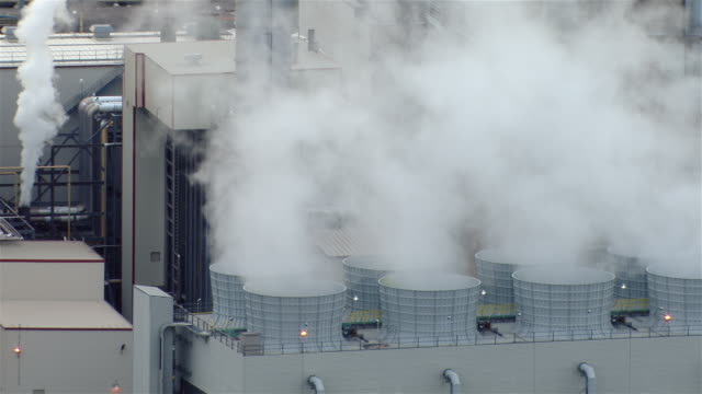 Aerial shot showing steam rising from cooling towers at the Linden Generating Station in New Jersey.