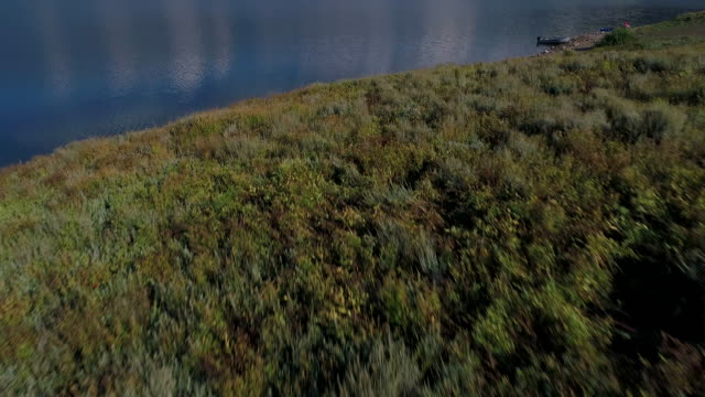Aerial shot soaring over mountain lake