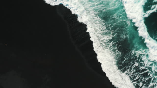 aerial shot spinning above waves rolling onto a black sand beach, lanzarote, spain - landscape scenery stock videos & royalty-free footage