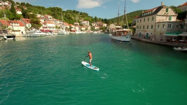 stockvideo's en b-roll-footage met luchtfoto sup stand up peddelen in kroatië - middellandse zee