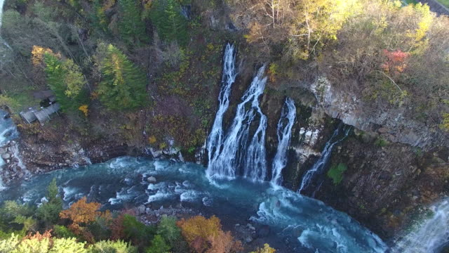Aerial shot taken by drone: Long shot of the Shirahige Falls and the Biei River