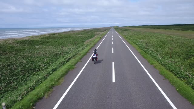 vídeos de stock, filmes e b-roll de aerial shot taken by drone:road bicycle moving along the japan sea ororon line - moving activity