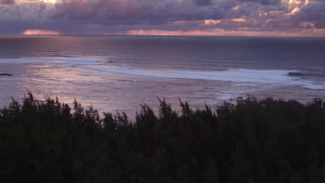 aerial shot tilting down on ocean during sunset - kahuku stock videos & royalty-free footage