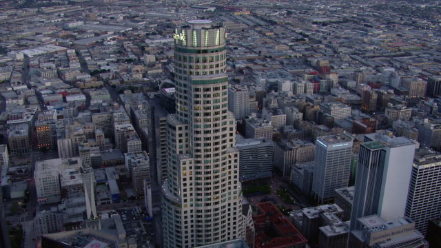 Aerial shot tilting down over the roof of the US Bank Tower in Downtown Los Angeles. The skyscraper is one of the tallest in the United States.