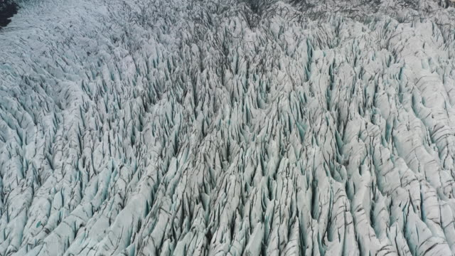 aerial shot tilting up to reveal the remote landscape surrounding skaftafell glacier, iceland - weathered stock videos & royalty-free footage