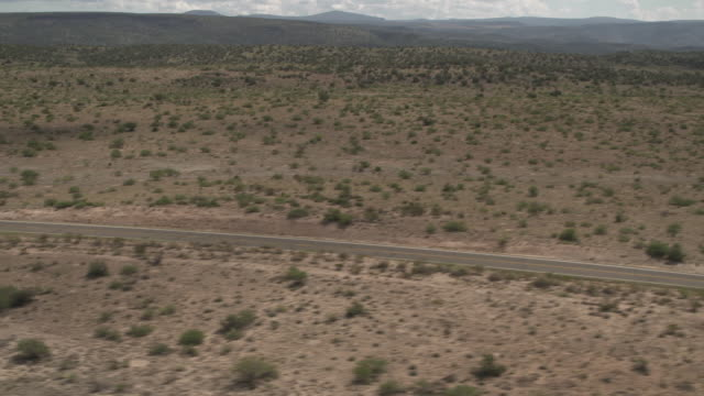 Aerial shot tracking left along a road that cuts through desert, western USA.