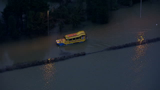 aerial shots duck tour amphibious vehicle driving down road through flood waters on in berkshire united kingdom - amphibious vehicle stock videos & royalty-free footage