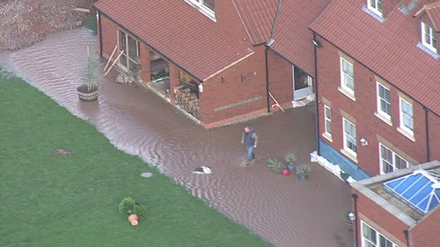 aerial shots flood water starts to breach flood defences of million pound house on the somerset levels. owner sam notaro has been using diggers to... - somerset stock videos & royalty-free footage