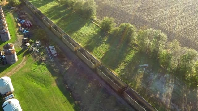 aerial shots fly over rows of grain silos at atheron grain in normandy illinois aerial shots follow a long train as it moves down a railroad track... - illinois stock-videos und b-roll-filmmaterial