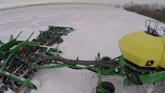 aerial shots focus on a john deere combine harvester sitting in the middle of a field covered in snow in bakken north dakota - north stock videos & royalty-free footage