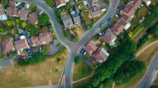 aerial shots following red car in suburbs. - part of a series stock videos & royalty-free footage